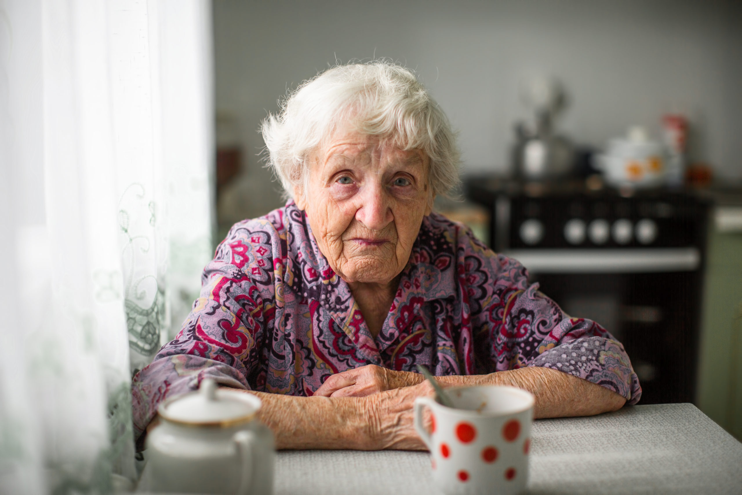 An elderly russian woman sitting at the kitchen table.